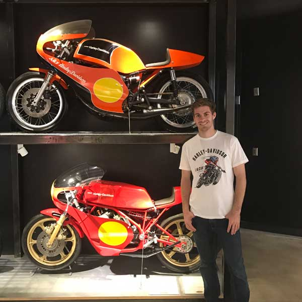 Andy DiBrino at Barber Motorcycle Museum standing with some classic motorcycles he'd like to throw a leg over