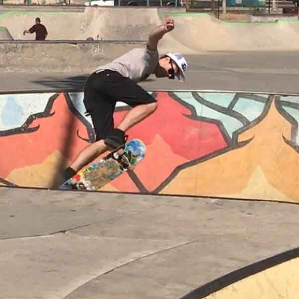 Andy shredding on a skateboard at a skate park caught in air