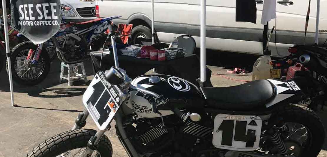 The set up for the weekend two flat track motorcycles and the black and white See See built Harley Davidson Hooligan motorcycle, with a set up to sell some See See swag
