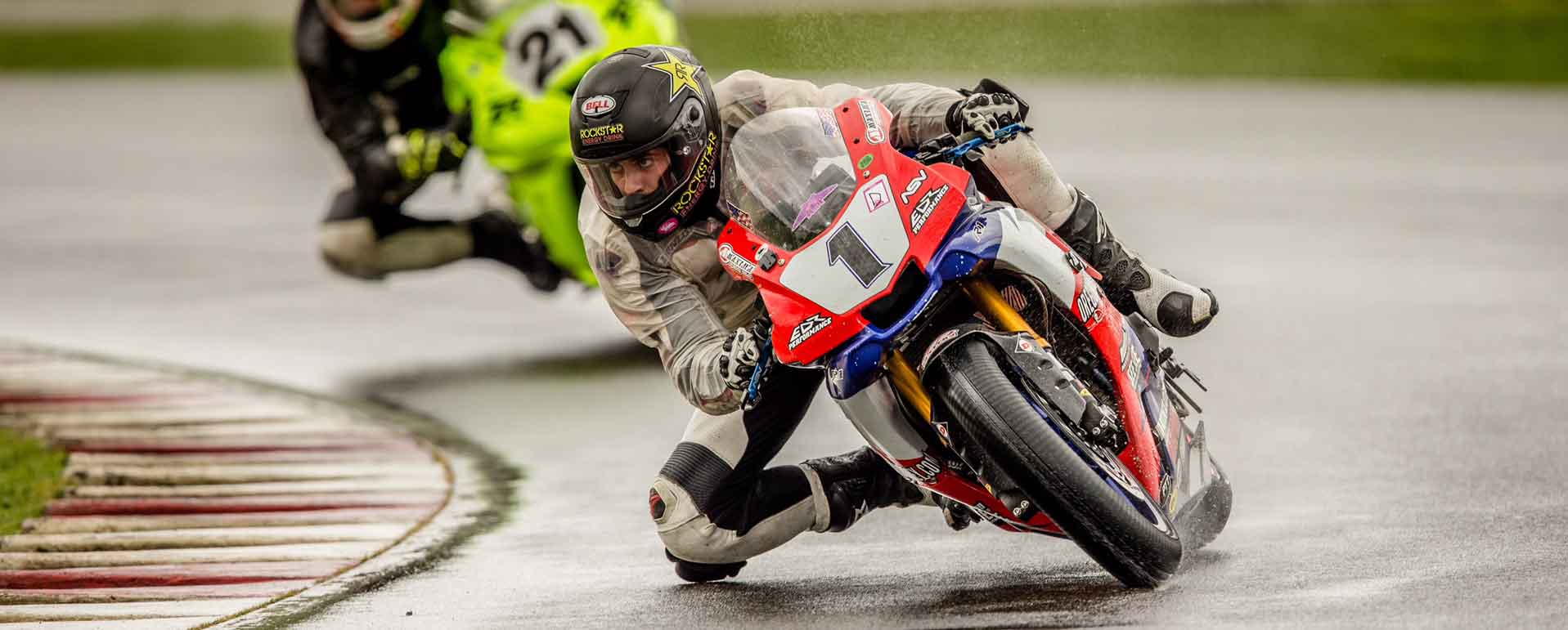Andy DiBrino leaning hard into a turn at OMRRA round 1 at PIR in wet rainy conditions